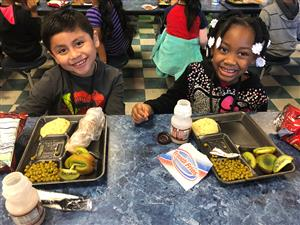 Two smiling elementary students sitting at a cafeteria table with their lunches set out before them.
