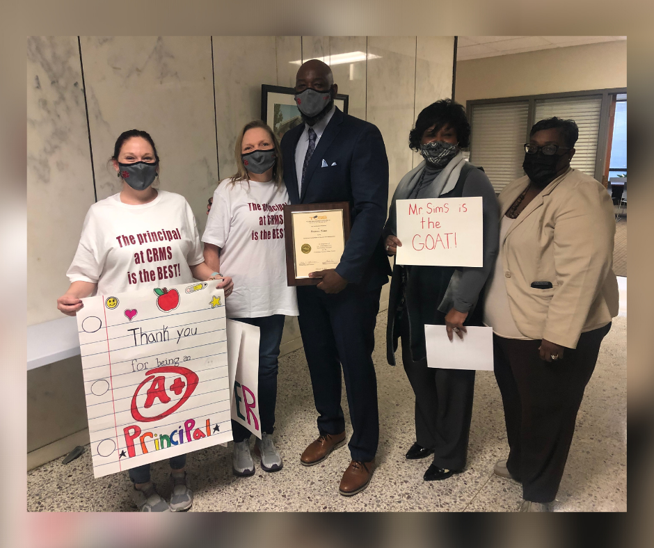 photo of Mr. Steve Sims with staff members holding congratulatory signs