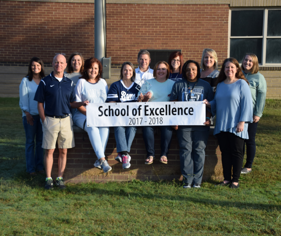 Northside faculty and staff with school of excellence banner.