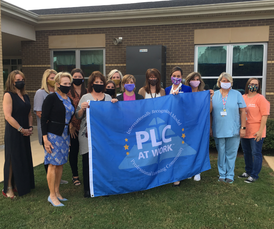 faculty and staff holding the Model PLC flag