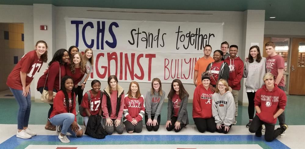Students dressed for team colors day with bullying prevention sign in background.