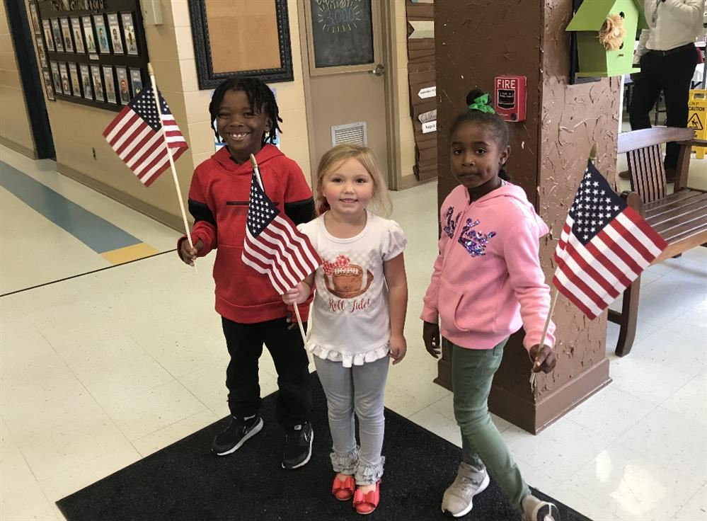 Three students holding American flags.
